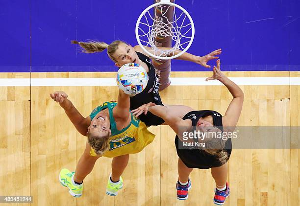 Caitlin Bassett of the Diamonds is challenged by Leana de Bruin and Casey Kopua of New Zealand during the 2015 Netball World Cup match between...