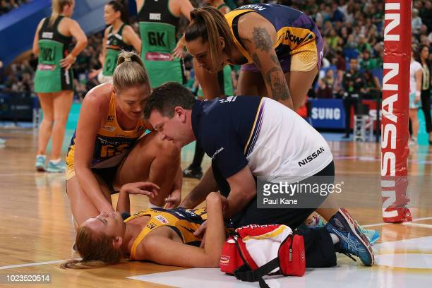 Caitlin Bassett of the Lightning and a team offical attend to Stephanie Wood of the Lightning during the Super Netball Grand Final match between the...
