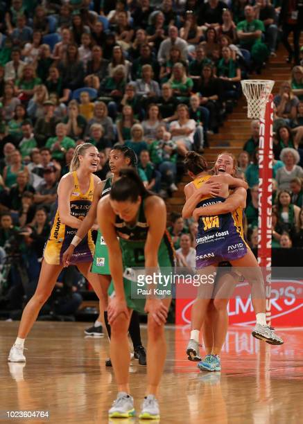 Caitlin Bassett Stephanie Wood and Kelsey Browne of the Lightning celebrate victory as Verity Charles of the Fever reacts to being defeated during...