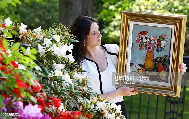 Caitlin Cruckshanks from Lyon Turnbull holds a still life by Scottish Colourist George Leslie Hunter called Still Life with Fruit and Anemones at...