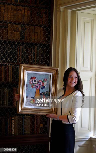 Caitlin Cruckshanks from Lyon & Turnbull holds a still life by Scottish Colourist George Leslie Hunter called Still Life with Fruit and Anemones at...