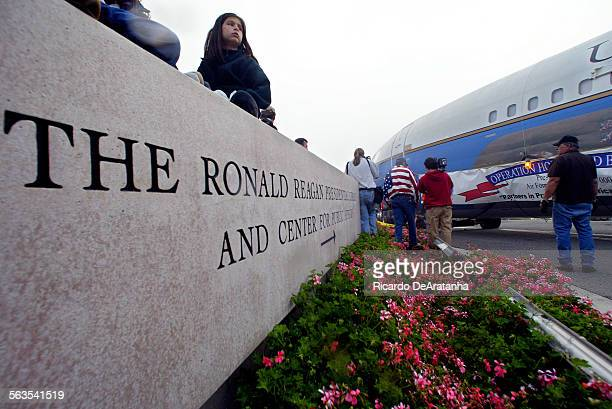 Caitlin Drake of Los Angeles sitting on the sign at the gate to the Reagan library watching Air Force One going by This was Operation Homeward Bound...