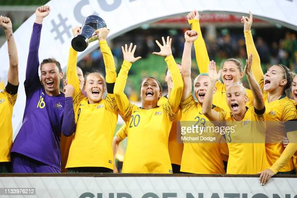 Caitlin Foord of the Matildas holds up the trophy next to Sam Kerr of the Matildas as they celebrate the win with teammates during the Cup of Nations...