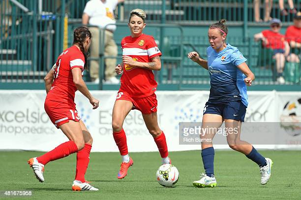 Caitlin Foord of the Sky Blue FC controls the ball against the defense of Brittany Taylor and Michelle Heyman of the Western New York Flash during...