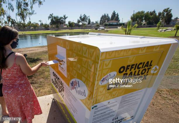 Caitlin Harjes, of Orange, places her ballot inside an official Orange County Registrar of Voters ballot Drop Box for the 2020 Presidential General...