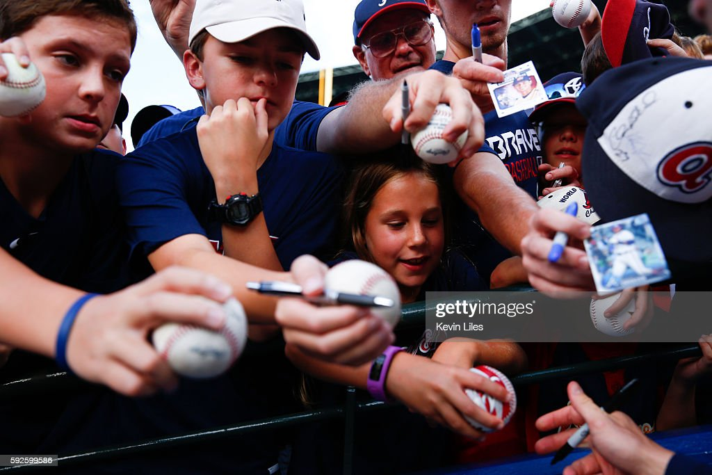 Caitlin Herhold, 9, center, gets a baseball signed byDansby Swanson #2 of the Atlanta Braves prior to the game against the Washington Nationals at Turner Field on August 20, 2016 in Atlanta, Georgia.