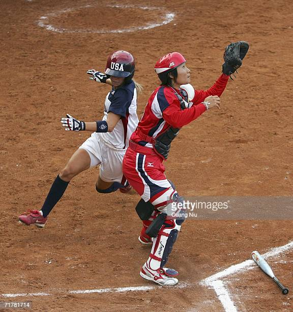 Caitlin Lowe of USA runs to the home plate as Emi Inut of Japan waits for a ball at ISF XI Women's Fast Pitch Softball World Championship at the...
