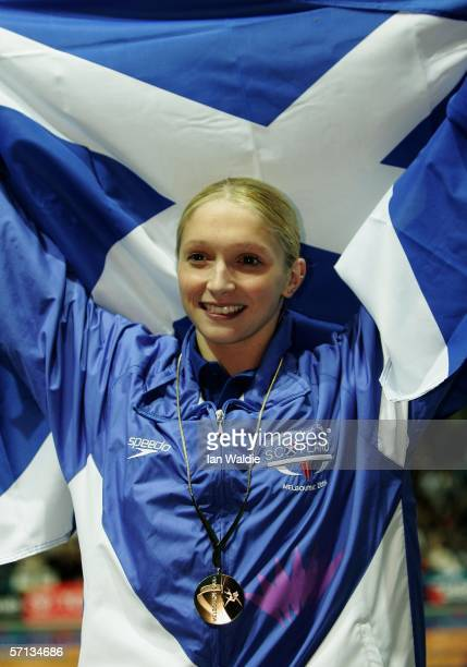 Caitlin McClatchey of Scotland waves to the crowd as she celebrates winning the gold the women's 400m freestyle final at the swimming held at the...