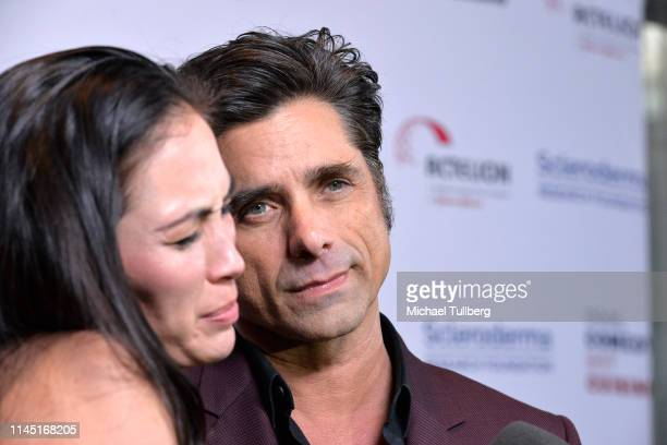 Caitlin McHugh and John Stamos attend Bob Saget's Cool Comedy Hot Cuisine presented by the Scleroderma Research Foundation at the Beverly Wilshire...