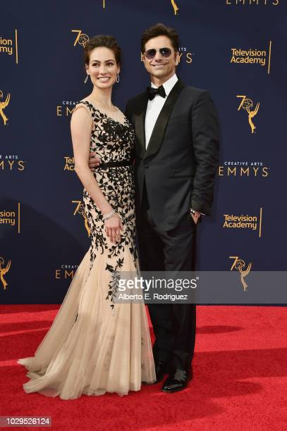 Caitlin McHugh and John Stamos attend the 2018 Creative Arts Emmy Awards at Microsoft Theater on September 8 2018 in Los Angeles California