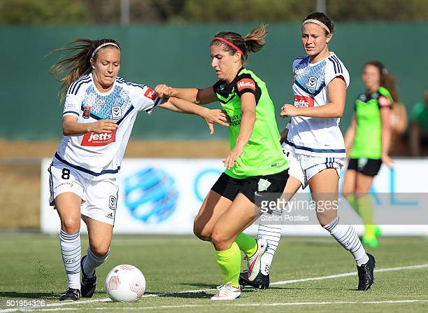 Caitlin Munoz of Canberra United and Jamie Pollock of Melbourne Victory contest possession during the round 10 WLeague match between Canberra United...