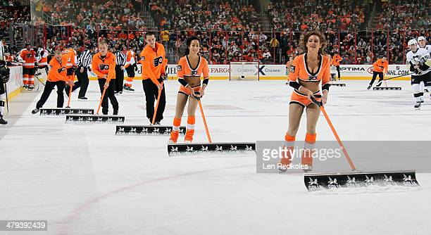 Caitlin Quack and Erika Choi Smith of the Philadelphia Flyers ice girls clean the ice during a stoppage in play against the Pittsburgh Penguins on...