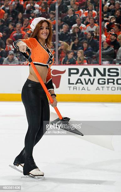 Caitlin Quirk of the Philadelphia Flyers ice girls cleans the ice during a timeout against the Carolina Hurricanes on December 13 2014 at the Wells...