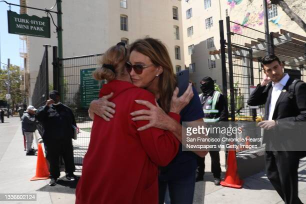 Caitlyn Jenner hugs Lisa Strawn, a desk clerk, during a media event outside the Turk-Hyde Mini Park during a tour the Tenderloin on Wednesday, August...
