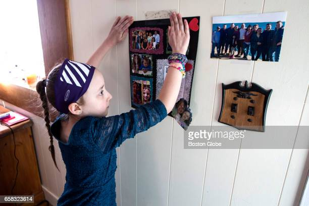 Caitlyn Rose Kasper hangs a family history project she made in school on the wall of her home before logging onto Ancestrycom to learn her genetic...