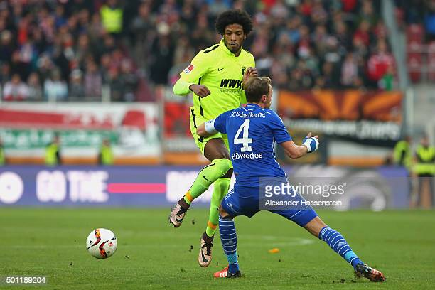 Caiuby Francisco da Silva of Augsburg battles for the ball with Benedikt Hoewedes of Schalke during the Bundesliga match between FC Augsburg and FC...