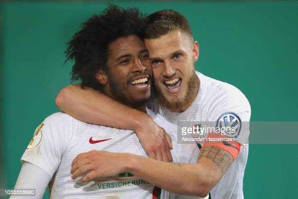 Caiuby Francisco da Silva of Augsburg celebrates scoring the winning goal with his team mate Jeffrey Gouweleeuw during the DFB Cup match between FC...