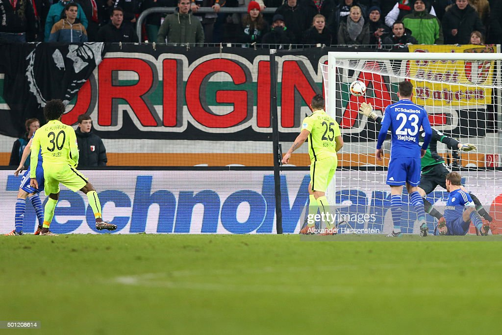 Caiuby Francisco da Silva (L) of Augsburg scores the winning goal during the Bundesliga match between FC Augsburg and FC Schalke 04 at WWK Arena on December 13, 2015 in Augsburg, Germany.