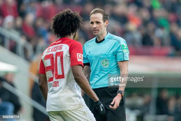 Caiuby Francisco da Silva of Augsburg speaks with Referee Sascha Stegemann during the Bundesliga match between FC Augsburg and SV Werder Bremen at...