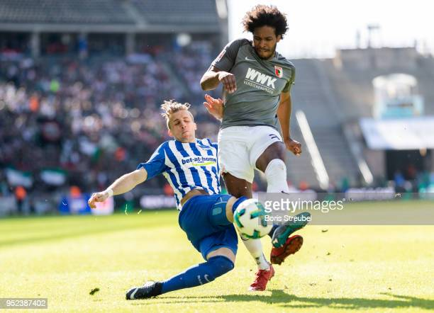 Caiuby Francisco da Silva of FC Augsburg is tackled by Peter Pekarik of Hertha BSC during the Bundesliga match between Hertha BSC and FC Augsburg at...