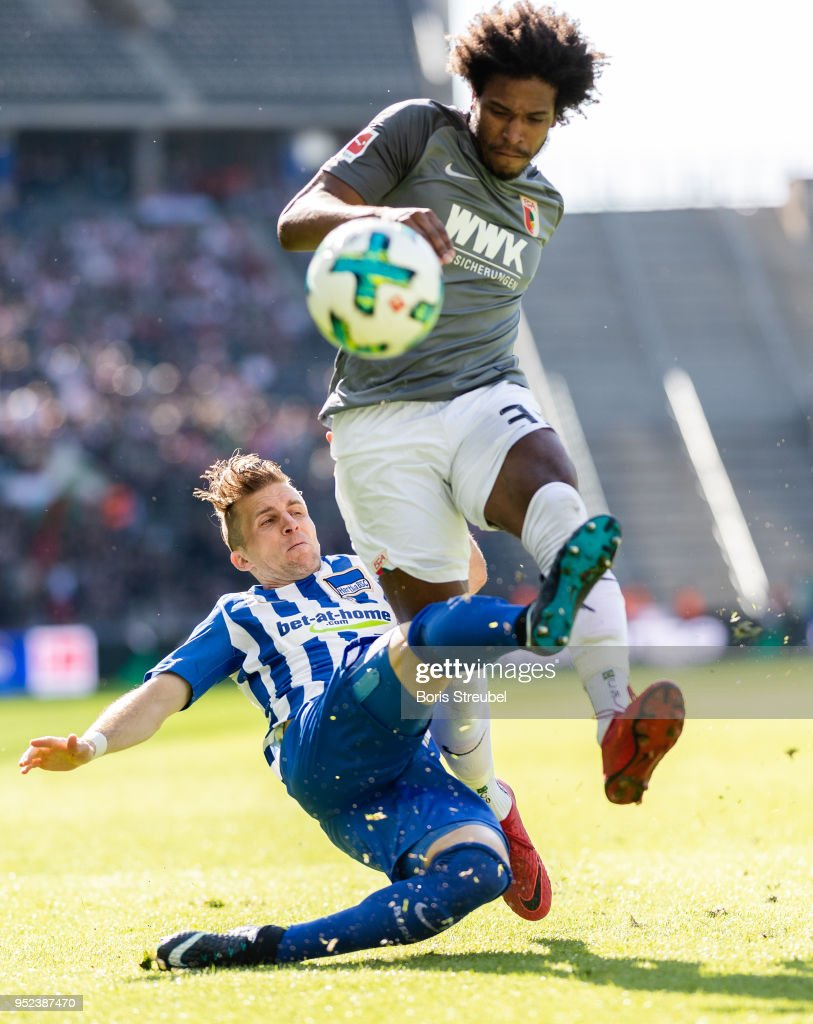 Caiuby Francisco da Silva of FC Augsburg is tackled by Peter Pekarik of Hertha BSC during the Bundesliga match between Hertha BSC and FC Augsburg at Olympiastadion on April 28, 2018 in Berlin, Germany.