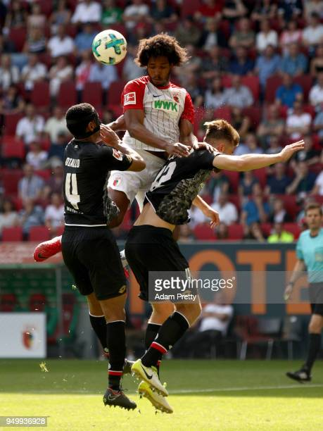 Caiuby of Augsburg and Abdou Lakhad Diallo and Alexander Hacker of Mainz jump to head for the ball during the Bundesliga match between FC Augsburg...