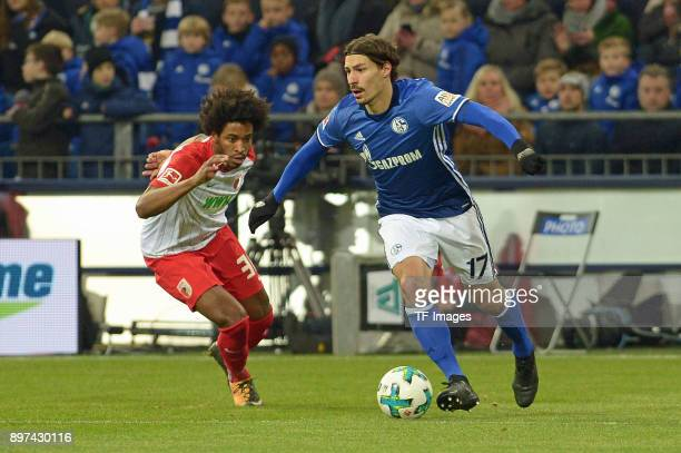 Caiuby of Augsburg and Benjamin Stambouli of Schalke battle for the ball during the Bundesliga match between FC Schalke 04 and FC Augsburg at...