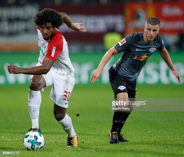 Caiuby of Augsburg as Diego Demme of Leipzig looks on during the Bundesliga match between FC Augsburg and RB Leipzig at WWK-Arena on September 19,...