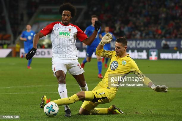 Caiuby of Augsburg is fouled by Koen Casteels of Wolfsburg during the Bundesliga match between FC Augsburg and VfL Wolfsburg at WWKArena on November...