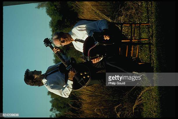 Cajun performer Felix Richard sits in a chair as he plays the accordion Standing next to him his son Sterling plays the guitar Cankton Louisiana USA...