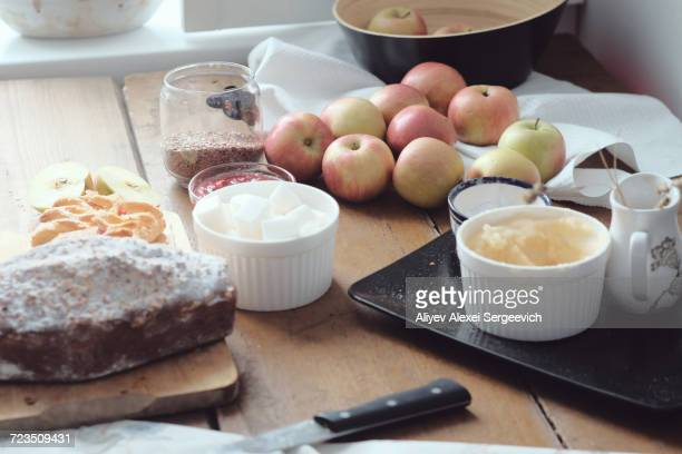Cake and desert ingredients with apples on kitchen table
