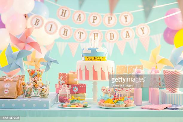cake, candy and gifts at birthday party - birthday cake stock photos and pictures