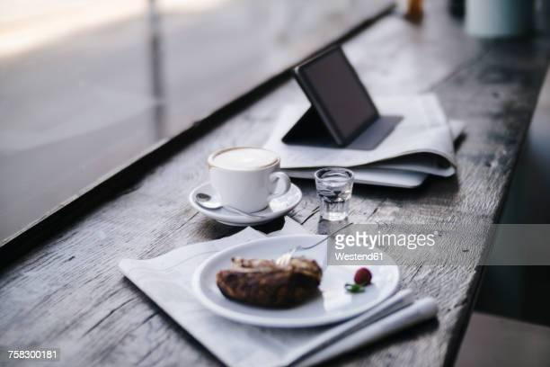 cake, coffee and tablet pc on a shelf in a cafe - empty paper plate stock photos and pictures