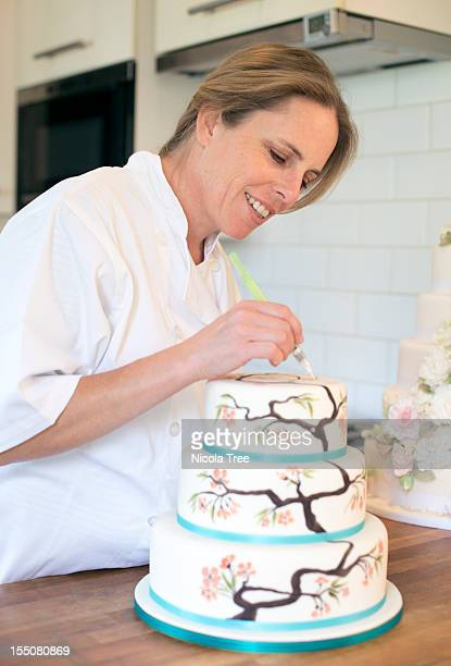 a cake maker decorating a cake - decorating a cake stock pictures, royalty-free photos & images