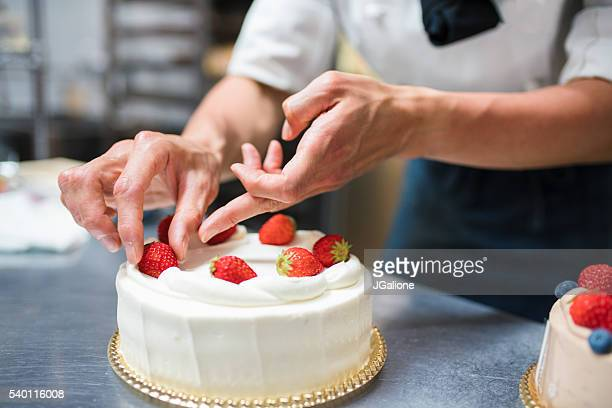 Cake maker placing strawberries on a cake