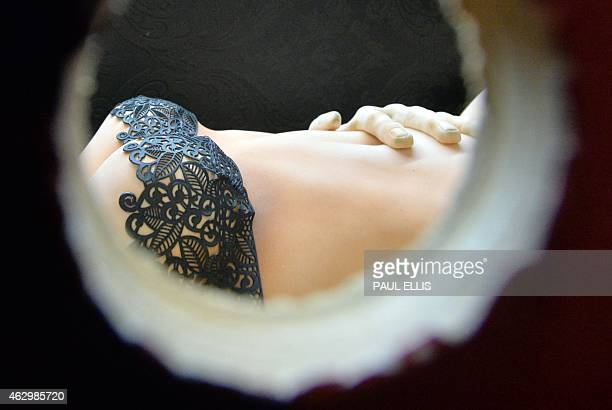 A cake model of a women is seen through a peephole in an exhibit depicting the book and film Fifty Shades of Grey during the final day of the Cake...