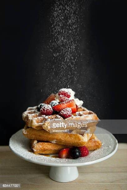 Cake stand of Belgian waffles with different berries sprinkled with icing sugar