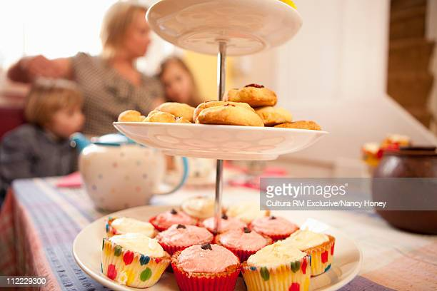Cake stand of cupcakes with family in the background
