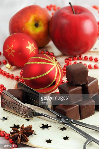 Cake tong holding Dominosteine cookie with Christmas ornaments background