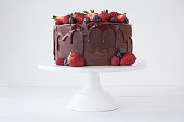 Cake with chocolate, decorated with various berries on a white table.