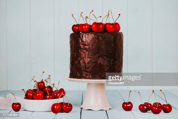Cake with chocolate icing and cherries on cake stand
