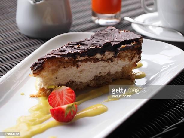 Kuchen mit Tofu und Schokolade, Vanille-sauce, Erdbeere auf einem Tisch