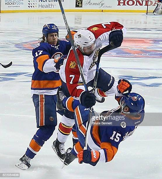 Cal Clutterbuck and Matt Martin of the New York Islanders go up against Dmitry Kulikov of the Florida Panthers during the first period during Game...