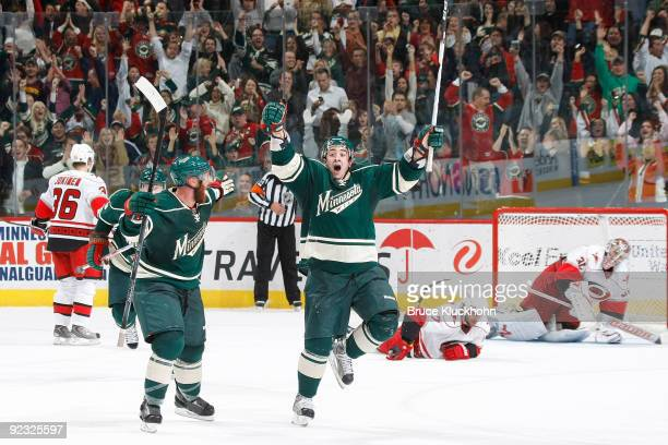 Cal Clutterbuck celebrates with his Minnesota Wild teammate Greg Zanon after scoring the game winning goal in overtime against the Carolina...