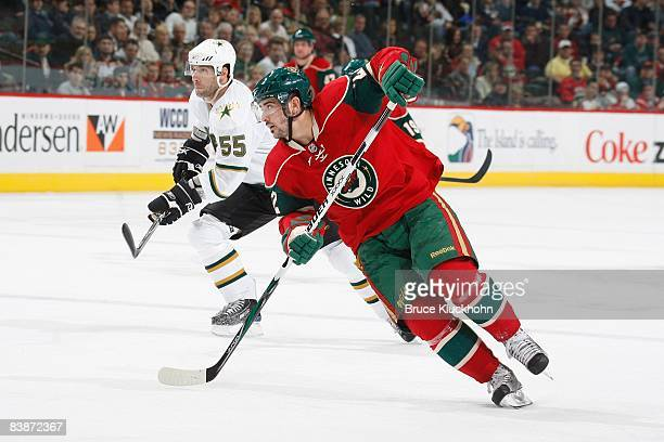 Cal Clutterbuck of the Minnesota Wild and Darryl Sydor of the Dallas Stars skate to the puck during the game at the Xcel Energy Center on November 26...