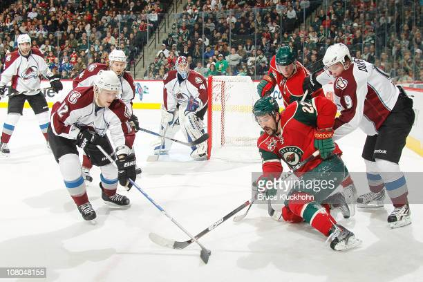 Cal Clutterbuck of the Minnesota Wild fights for puck possession against Kevin Porter of the Colorado Avalanche during the game at Xcel Energy Center...