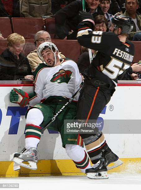 Cal Clutterbuck of the Minnesota Wild is checked by Brett Festerling of the Anaheim Ducks during the NHL game at Honda Center on December 14 2008 in...
