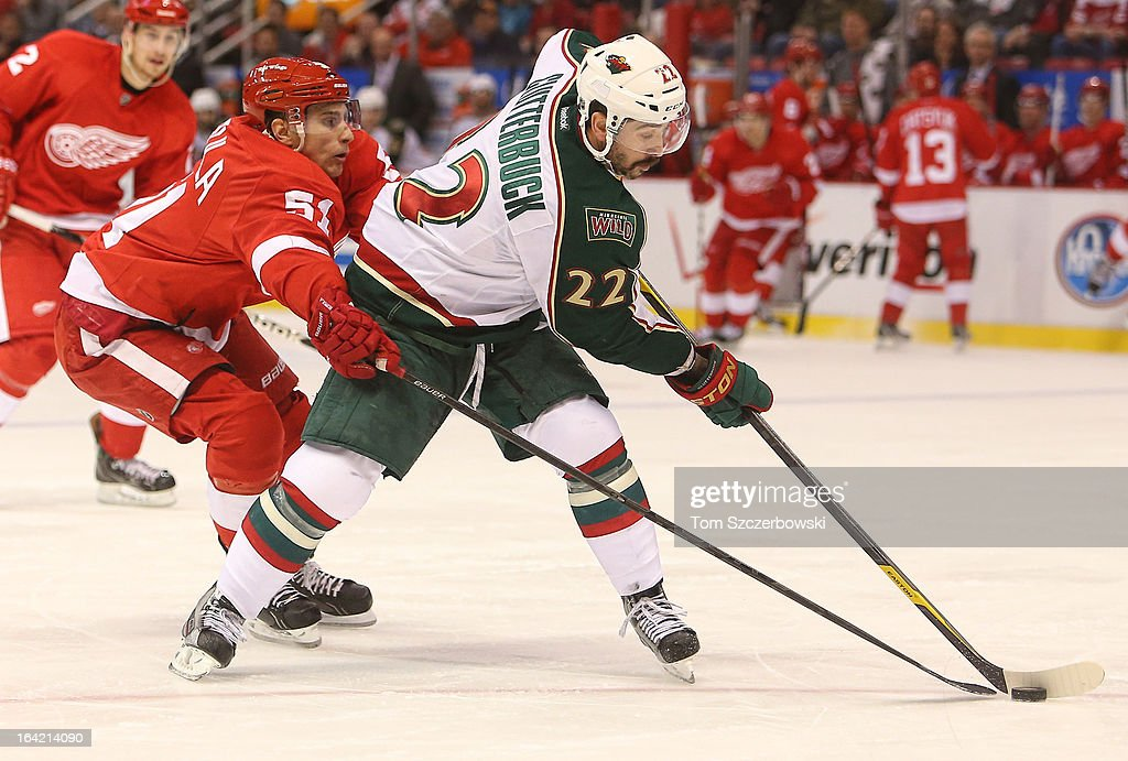 Cal Clutterbuck #22 of the Minnesota Wild is checked from behind by Valtteri Filppula #51 of the Detroit Red Wings in NHL action at Joe Louis Arena on March 20, 2013 in Detroit, Michigan.