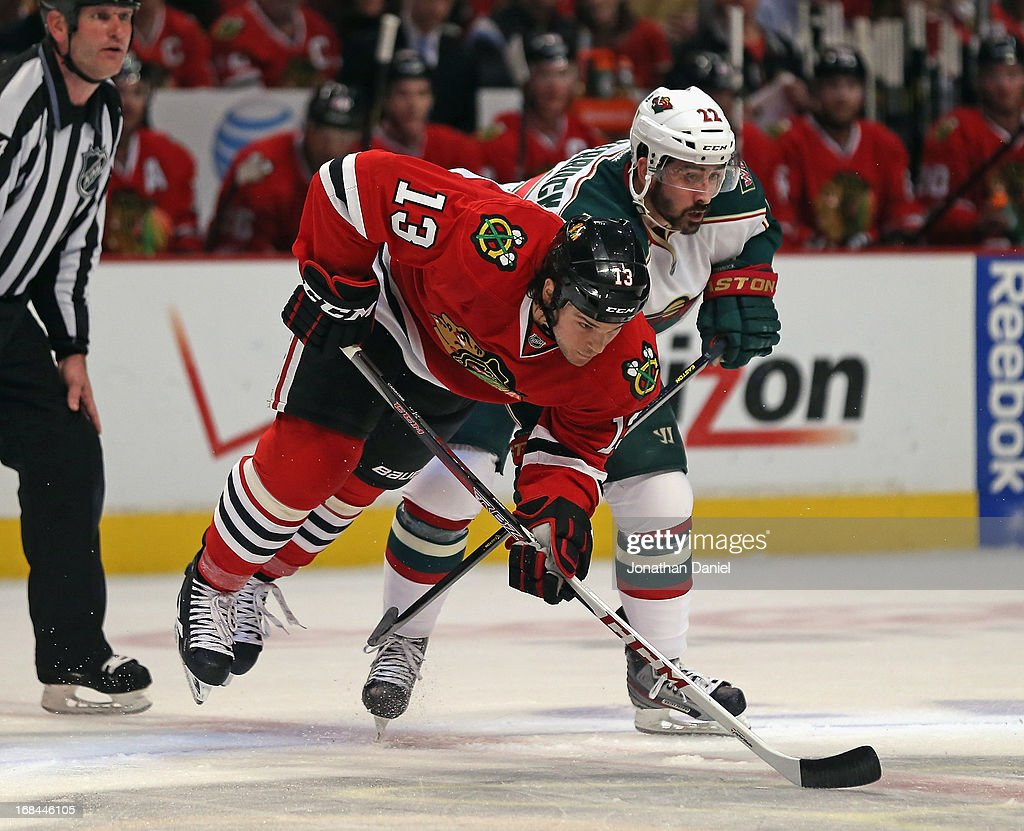 Cal Clutterbuck #22 of the Minnesota Wild trips Daniel Carcillo #13 of the Chicago Blackhawks as they wait for a face-off in Game Five of the Western Conference Quarterfinals during the 2013 NHL Stanley Cup Playoffs at the United Center on May 9, 2013 in Chicago, Illinois.