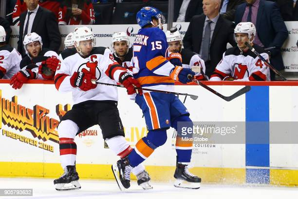 Cal Clutterbuck of the New York Islanders and Andy Greene of the New Jersey Devils battle for the puck during the second period at Barclays Center on...